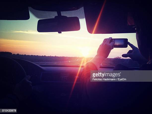Rear view of man using camera phone in the car