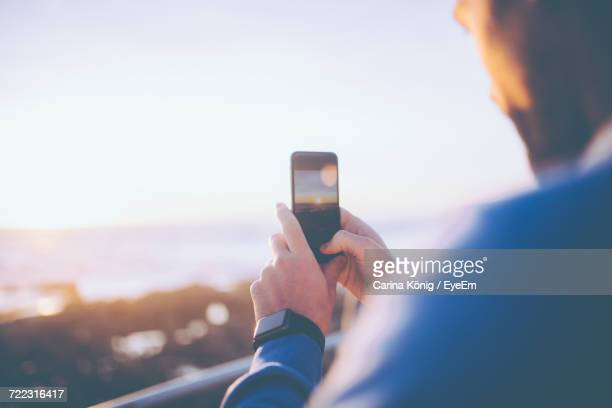 Rear View Of Man Using Mobile Phone At Beach