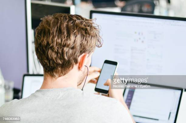 Rear View Of Man Using Phone At Office