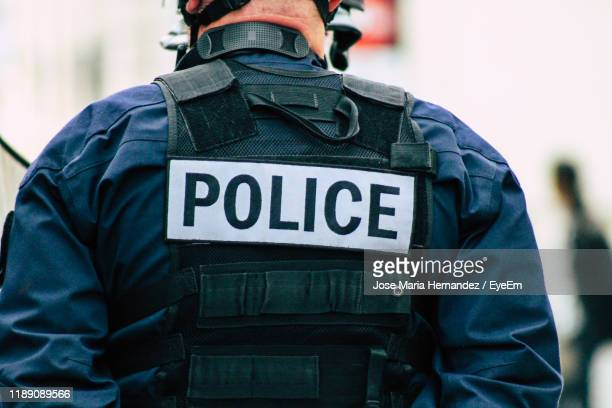 rear view of man using smart phone - police force stock pictures, royalty-free photos & images