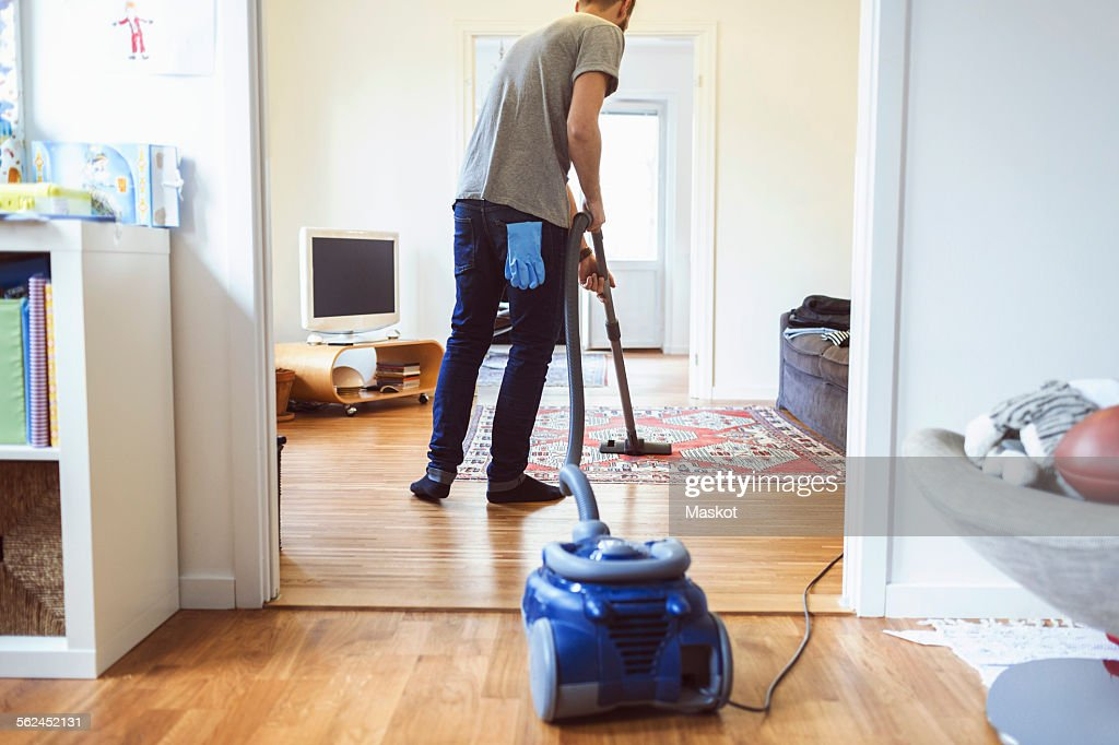 Rear view of man vacuuming carpet : Stock Photo