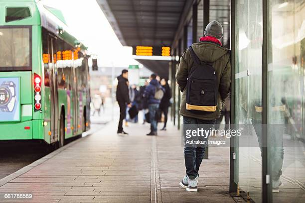 rear view of man waiting at bus stop - wachten stockfoto's en -beelden