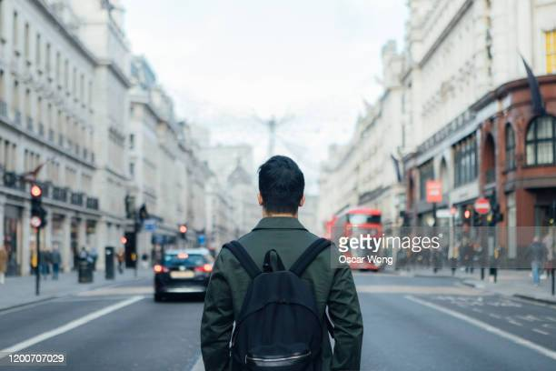 rear view of man waiting for uber on the high street in london - prosperity stock pictures, royalty-free photos & images