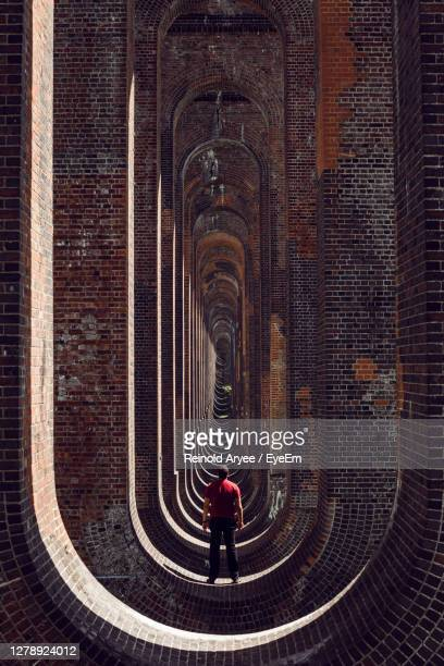 rear view of man walking against building - space mission stock pictures, royalty-free photos & images