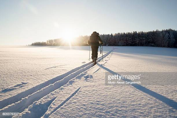 rear view of man walking along snow tracks, ural, russia - cross country skiing stock pictures, royalty-free photos & images