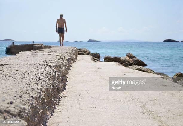 Rear view of man walking along wall by beach, Ibiza, Spain