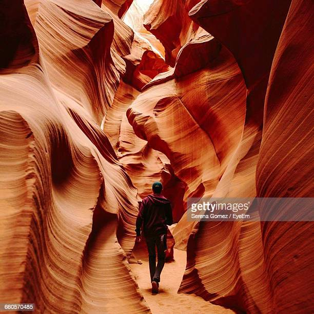 rear view of man walking amidst sandstones at antelope canyon - antelope canyon stock pictures, royalty-free photos & images