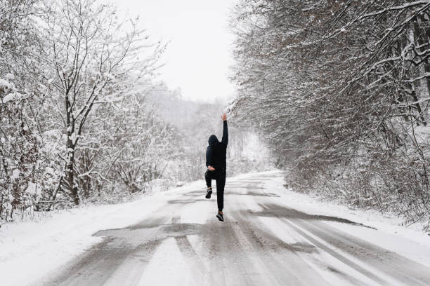 Rear View Of Man Walking And Jumping On Snow Covered Road