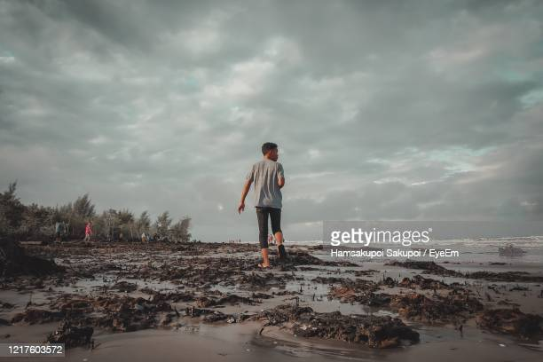rear view of man walking at beach against cloudy sky - hamsakupoi stock pictures, royalty-free photos & images