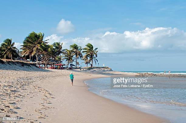 rear view of man walking at beach against cloudy sky - natal brazil stock pictures, royalty-free photos & images