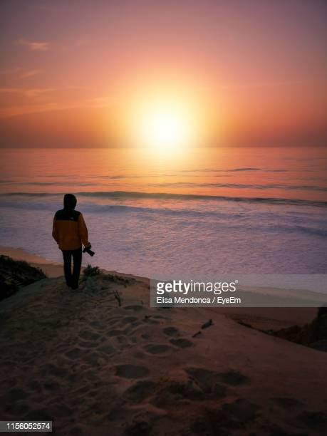 rear view of man walking at beach during sunset - comporta portugal stock photos and pictures