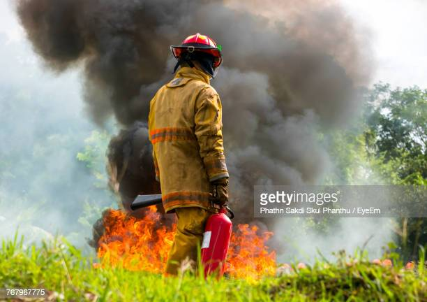rear view of man walking by fire - bushfires stock photos and pictures