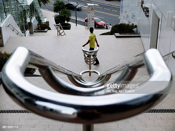 Rear View Of Man Walking Down Stairs