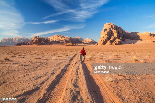 rear view of man walking in desert landscape with tire tracks leading to distant mountain. - jordan middle east stock pictures, royalty-free photos & images