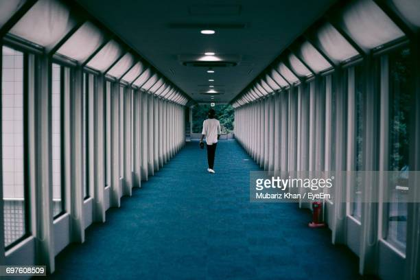 Rear View Of Man Walking In Empty Corridor Of Building