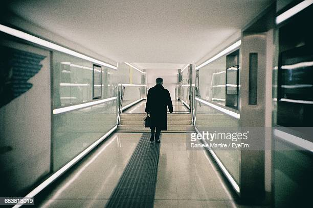 rear view of man walking in illuminated corridor - long coat stock pictures, royalty-free photos & images