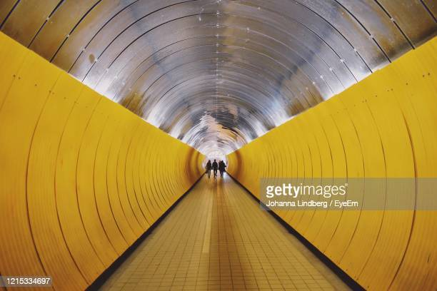 rear view of man walking in illuminated tunnel - travolator stock pictures, royalty-free photos & images
