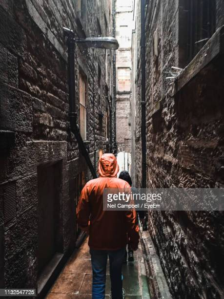 rear view of man walking in narrow alley - stone wall stock pictures, royalty-free photos & images