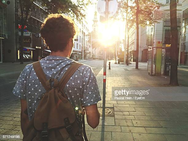Rear View Of Man Walking In Sidewalk In City At Morning