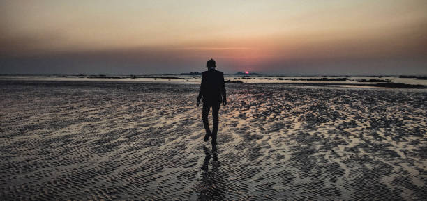Rear View Of Man Walking On A Beach During Sunset, Towards Oblivion.