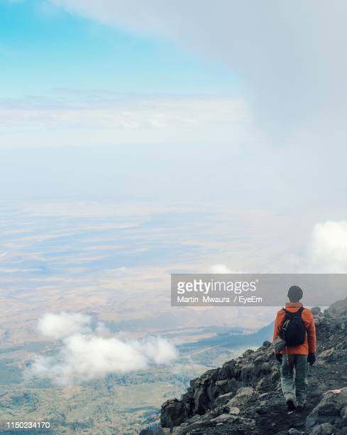 rear view of man walking on cliff against cloudy sky - arusha national park stock photos and pictures