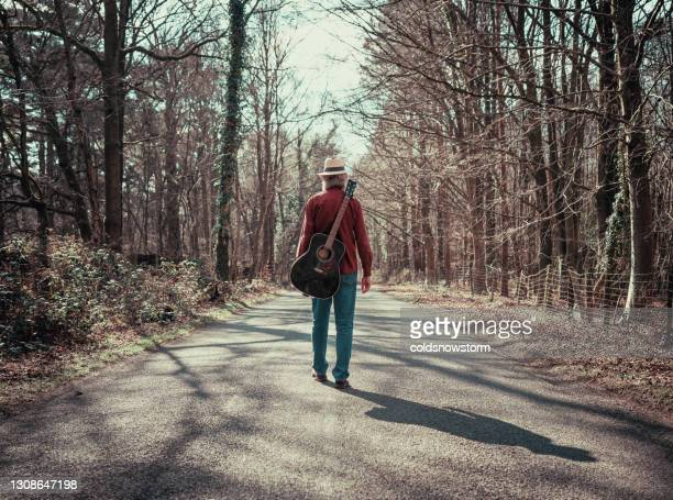 rear view of man walking on country road with guitar on his back - country and western stock pictures, royalty-free photos & images