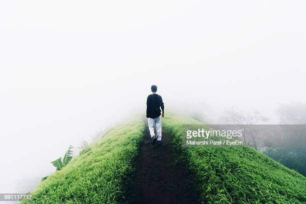 Rear View Of Man Walking On Dirt Road Amidst Grass On Hill During Foggy Weather