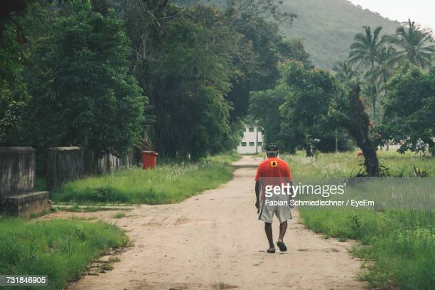 Rear View Of Man Walking On Dirt Road By Grassy Field