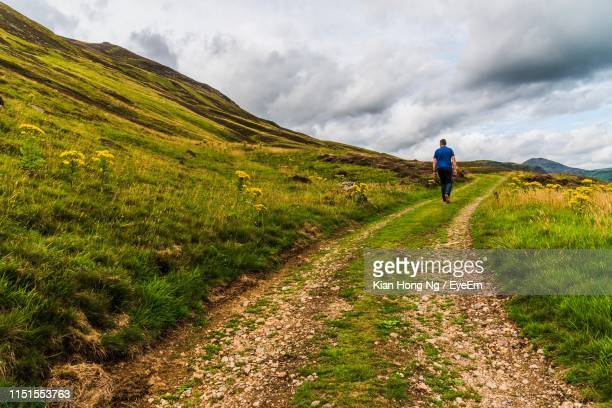 rear view of man walking on field against sky - モーレイ湾 ストックフォトと画像