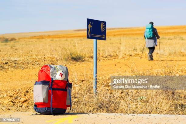 rear view of man walking on field against sky - santiago de compostela stock pictures, royalty-free photos & images