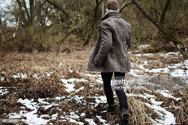 Rear View Of Man Walking On Field At Forest During Winter