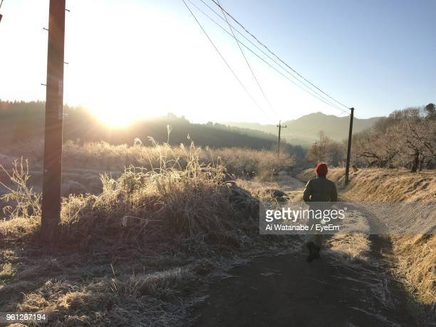 Rear View Of Man Walking On Field During Winter