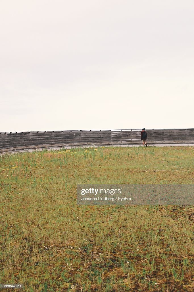 Rear View Of Man Walking On Field With Fence Against Clear Sky : Stock Photo