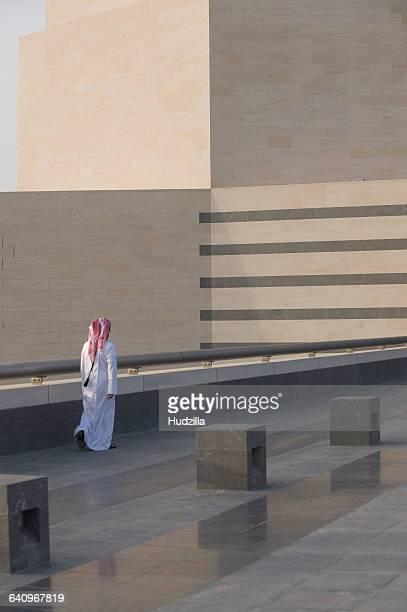 Rear view of man walking on floor by railing