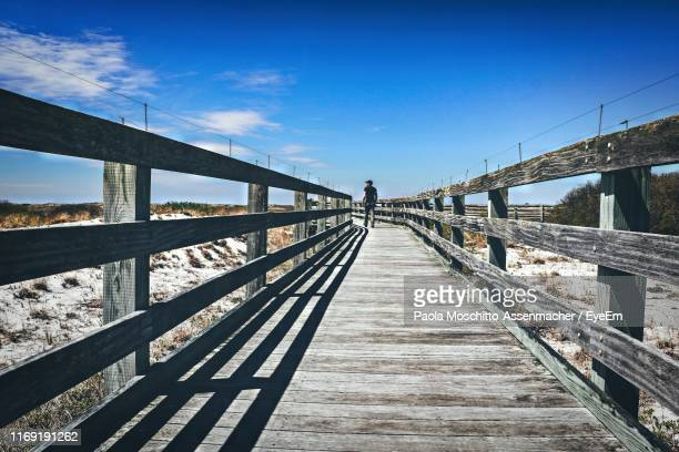 rear view of man walking on footbridge against blue sky - jones beach stock pictures, royalty-free photos & images