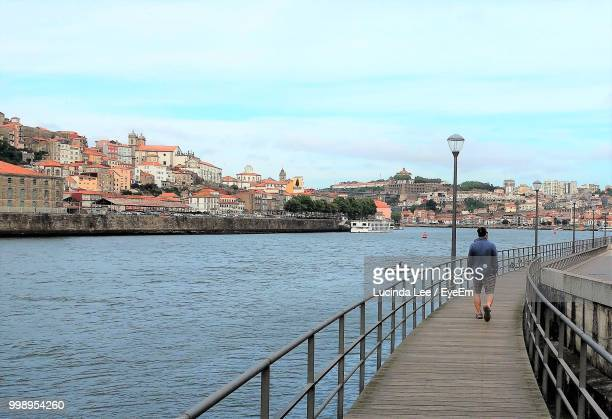 rear view of man walking on footbridge over river against sky - lucinda lee stock photos and pictures