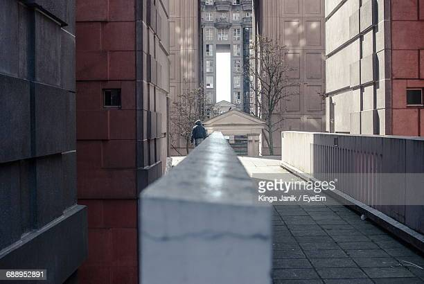 rear view of man walking on footpath amidst buildings - noisy le grand stock photos and pictures