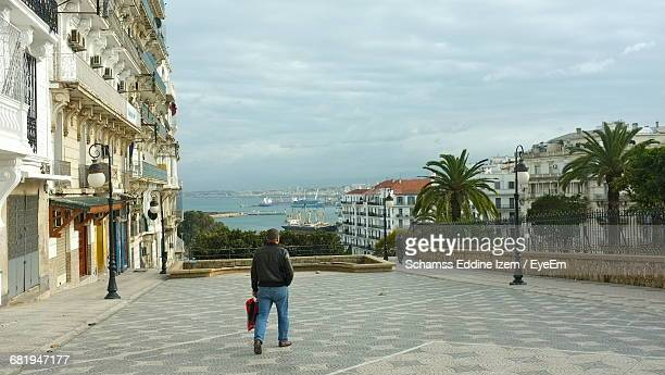 rear view of man walking on footpath in city against cloudy sky - alger photos et images de collection