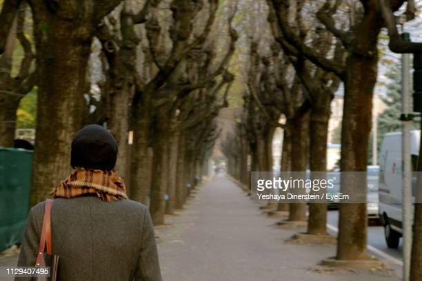 Rear View Of Man Walking On Footpath In City During Winter