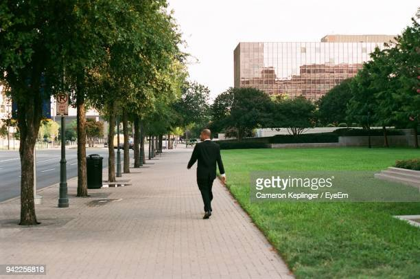 rear view of man walking on footpath in city - cameron young imagens e fotografias de stock