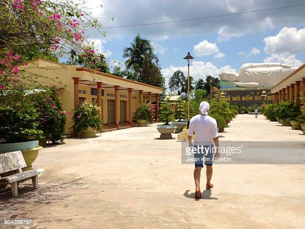 rear view of man walking on footpath with buddha statue at temple - human representation stock pictures, royalty-free photos & images