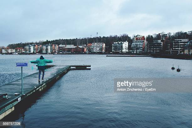 rear view of man walking on jetty - zinchenko stock pictures, royalty-free photos & images