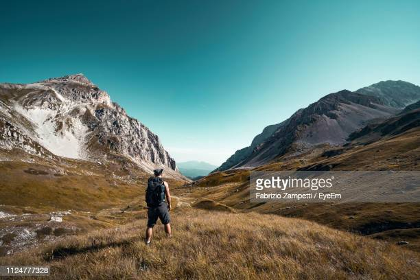 rear view of man walking on mountain against blue sky during winter - fabrizio zampetti foto e immagini stock