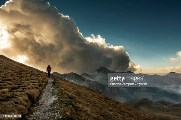 rear view of man walking on mountain against sky during sunset - fabrizio zampetti foto e immagini stock