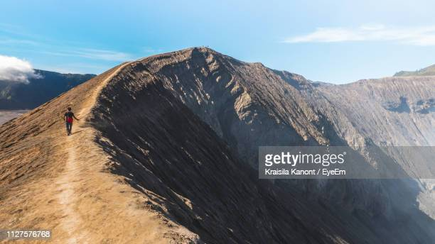 rear view of man walking on mountain against sky - bromo tengger semeru national park stock pictures, royalty-free photos & images