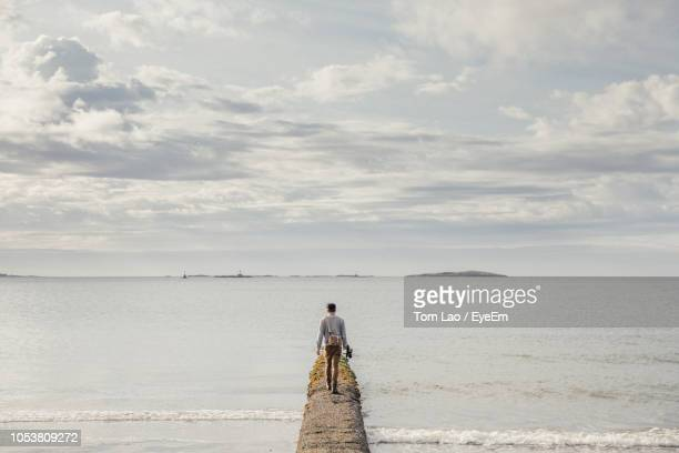 rear view of man walking on pier in sea against sky - victoria canada stock pictures, royalty-free photos & images