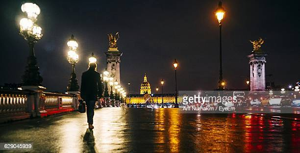 rear view of man walking on pont alexandre iii leading towards hotel des invalides at night - pont alexandre iii photos et images de collection