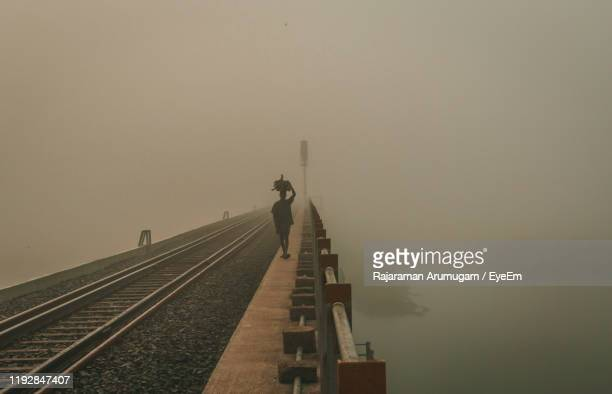 rear view of man walking on railway bridge amidst fog - tamil nadu stock pictures, royalty-free photos & images