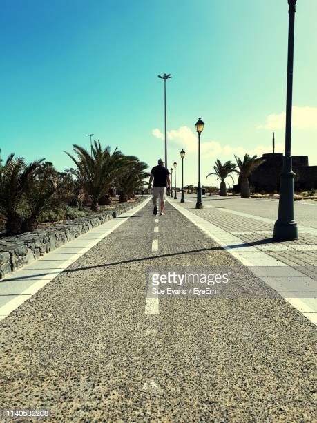 Rear View Of Man Walking On Road Against Blue Sky During Sunny Day