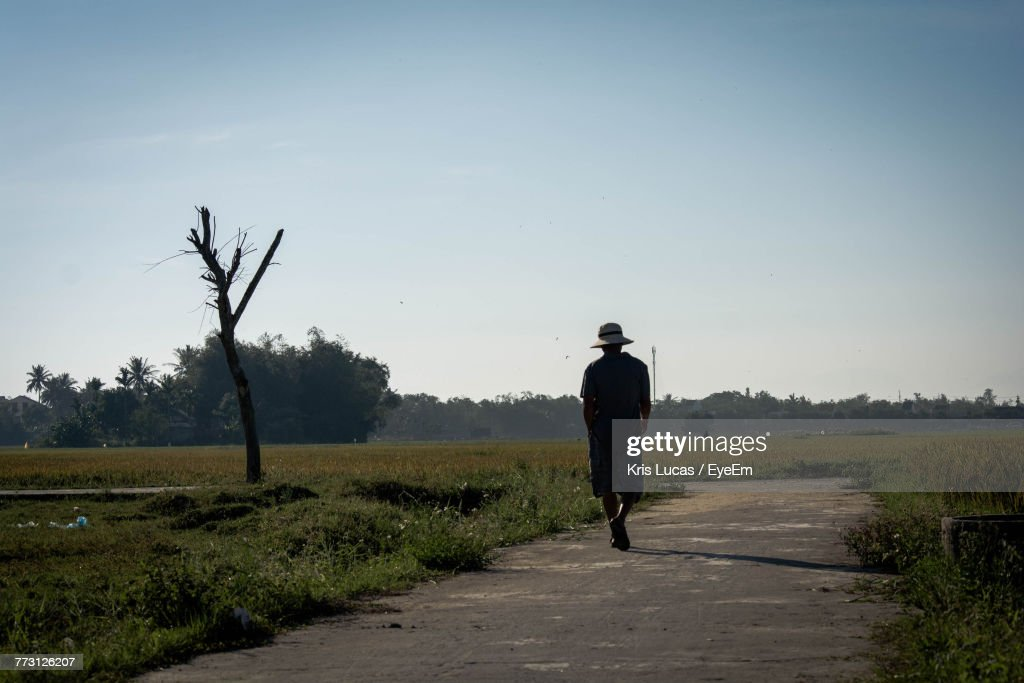 Rear View Of Man Walking On Road Against Sky : Stock Photo